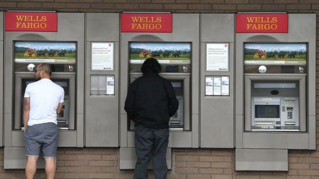 Dos personas usan los cajeros automáticos de Wells Fargo.