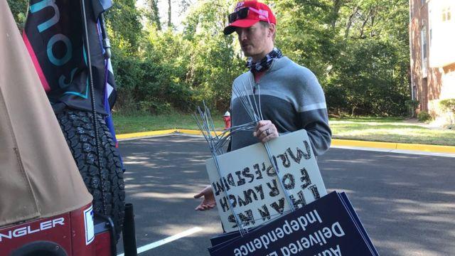 Scott Pio carries yard signs