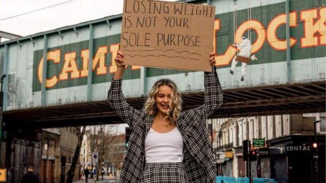 Lauren Black segurando um cartaz em que se lê: perder peso não é o seu único propósito