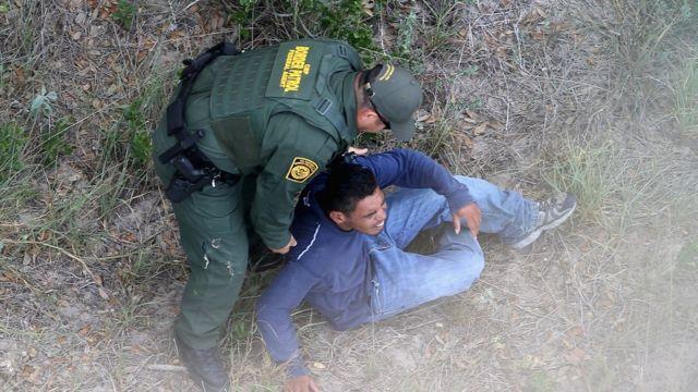 A US Border Patrol agent apprehends an undocumented immigrant near Falfurrias, Texas, on 25 July 2014