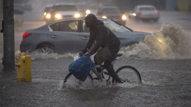 Hombre en bicicleta en medio de un aguacero