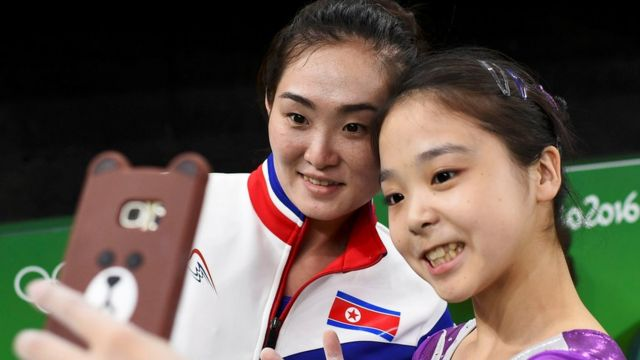Gymnasts Lee Eun-Ju of South Korea and Hong Un Jong of North Korea (PRK) take a selfie at the Rio Olympic Arena in 2016
