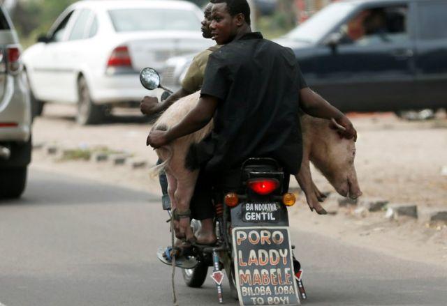 """Hanyuma rero, n'uyu mushoferi wa moto i Kinshasa, afite ubutumwa bwanditse inyuma kuri moto ye bugira buti - """"biloba loba to boyi"""" - bishatse kuvuga ngo, """"ntukite ku bitakureba""""."""