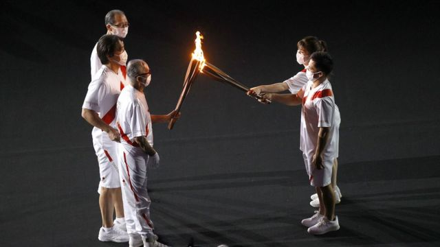 The torch carriers exchange the flame of the Olympic torch during the Opening Ceremony of the Tokyo 2020 Olympic Games at Olympic Stadium on July 23, 2021 in Tokyo, Japan.