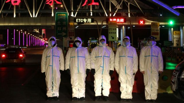 Police wearing protective suits block a road in Shijiazhuang