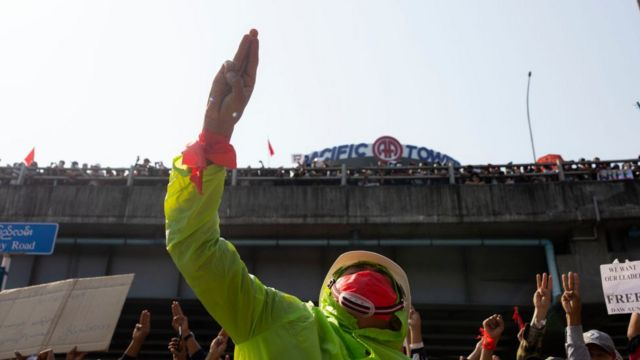 A protester wearing a mask makes a three-finger salute