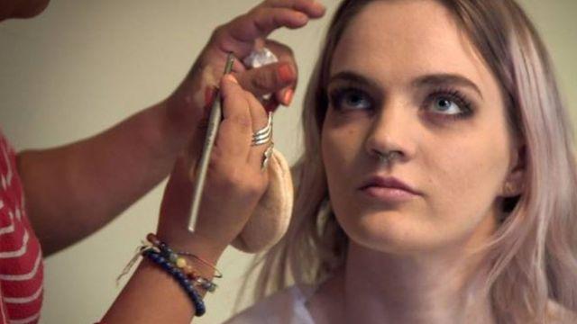 Una mujer maquillando a Jade para una escena.
