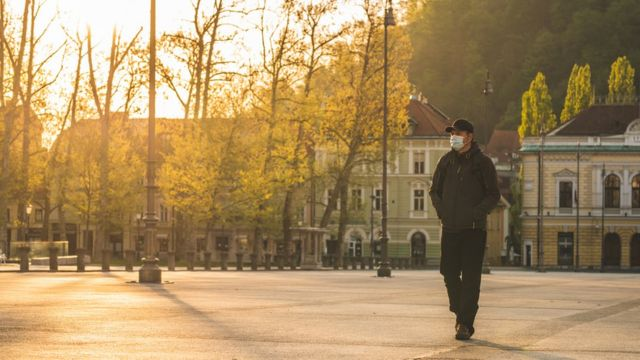 Man with mask walking through unoccupied city