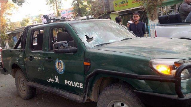 Bystanders look at a damaged Afghan police vehicle