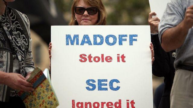 Manifestante com cartaz em que se lê: Madoff roubou, a SEC ignorou