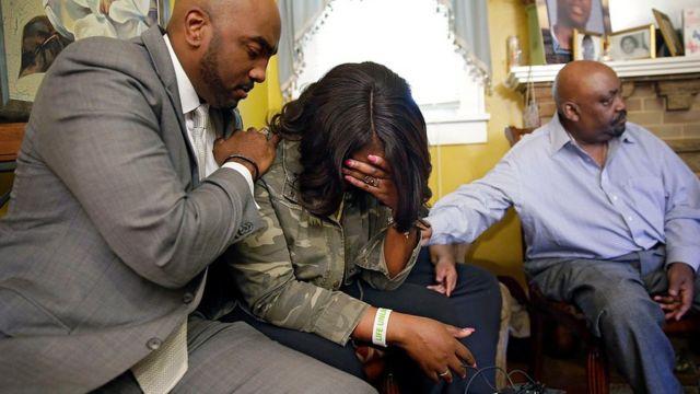 Tiffany (centro), hermana de Terence Crutcher, es consolada por el abogado de la familia, Damario Solomon-Simmons (izquierda), acompañados por el padre de la víctima, Joey (derecha).