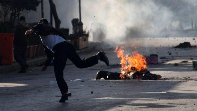 Süleymaniye'de bir gösterici yakılan lastiğe taş atıyor.