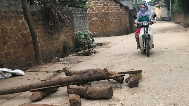 Một phụ nữ đi xe máy trên con đường làng có rải gạch và vài tấm gỗ chắn. Hình chụp ở xã Đồng Tâm, huyện Mỹ Đức, Hà Nội hôm 20/4/2017.