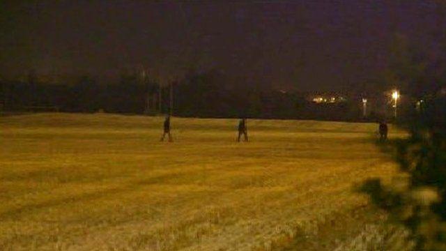 Migrants cross fields behind the village of Frethun, Calais