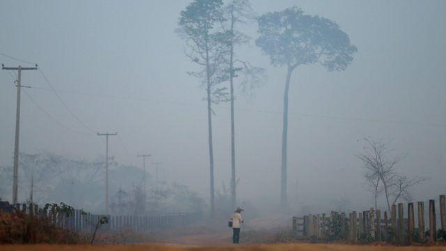 Homem caminha em estrada em Porto Velho em meio a fumaça