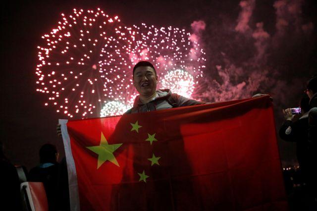 ชายชาวจีนร่วมฉลองการเริ่มต้นเทศกาลตรุษจีน ในย่านแมนฮัตตันขณะที่มีการแสดงดอกไม้ไฟและพลุอย่างสวยงาม เมื่อวานนี้ (14 ก.พ.)