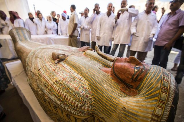 "Employees of Egypt""s ministry of antiquities observe a sarchphagus displayed in front of Hatshepsut Temple in Egypt""s valley of the Kings in Luxor on October 19, 2019"