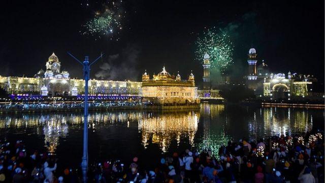 भारतको अमृतसरस्थित गोल्डन टेम्पलमा आतसबाझी हेर्दै भक्तजनहरू