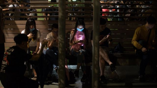 People use their mobile phones in a park near the Legislative Council building during a rally against amendments to an extradition bill in Hong Kong, China, early 12 June 2019