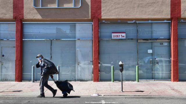 man walks past closed stores in US