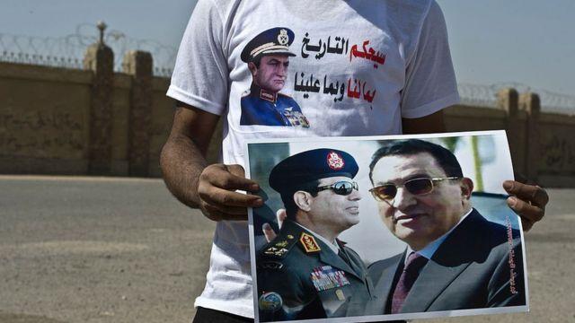 رجل يحمل لافتة تجمع بين مبارك والسيسي (أرشيفية)