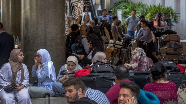 Para pegiat berunjuk rasa di Bandara Internasional Los Angeles (LAX), AS pada hari pertama penerapan kembali sebagian larangan perjalanan Trump, yang sementara melarang pendatang dari enam negara mayoritas Muslim.