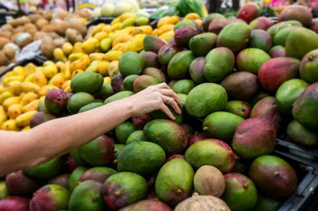 Woman picking a fresh mango at the market.