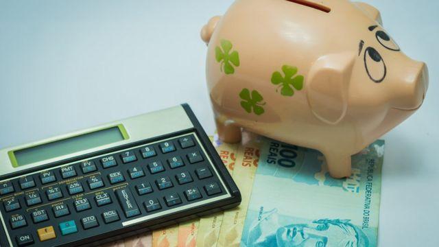 Porquinho, dinheiro e calculadora