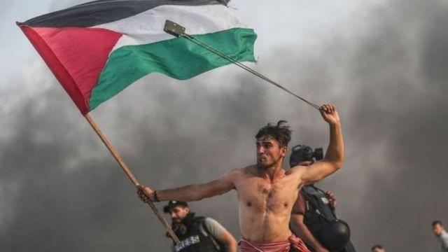 شاب عاري الصدر يحمل العلم الفلسطيني بيمينه ومقلاعا في يساره. صورة بعدسة الصحفي المصور محمد حسونة