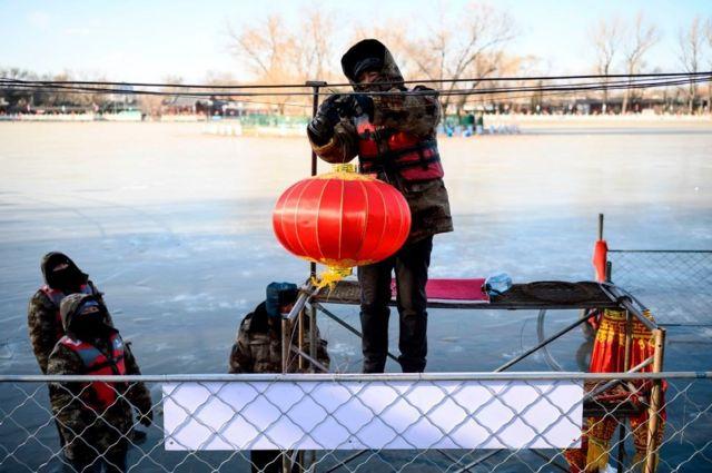 中国即将迎来春节。一名工作人员正在北京什刹海附近悬挂灯笼。