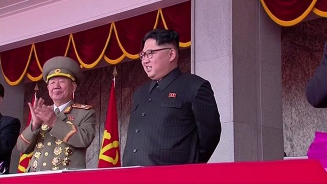 Kim Jong-un, smiling alongside a senior military official, on the podium above the event