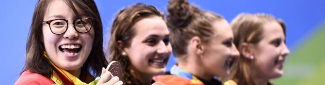 Fu Yuanhui grinning broadly on the podium after winning the backstroke 100m