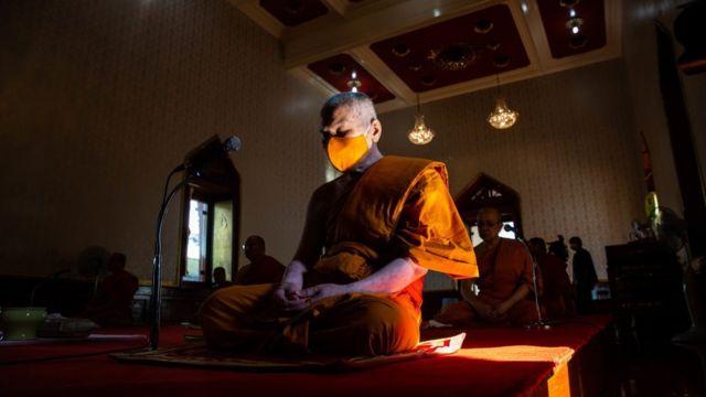Tối trước hôm tình trạng khẩn cấp có hiệu lực, một vị sư đeo khẩu trang tụng kinh cầu nguyện cho Thái Lan chóng qua cơn dịch bệnh