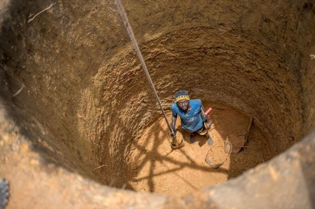A workman pauses from digging a well for the new settlement in Six Mile