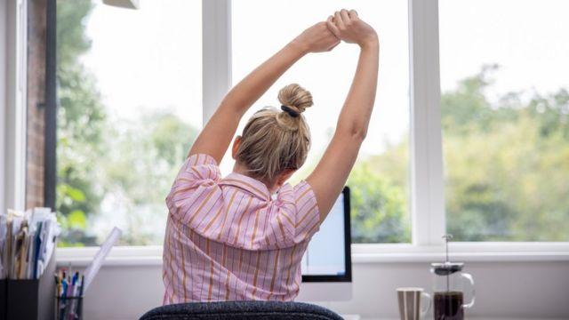 Una mujer de espaldas frente a una pantalla estira sus brazos.