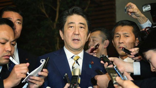 Japanese Prime Minister Shinzo Abe (C) speaks to reporters