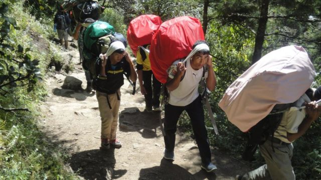 Teenagers working as porters carry heavy loads up to Everest Base Camp