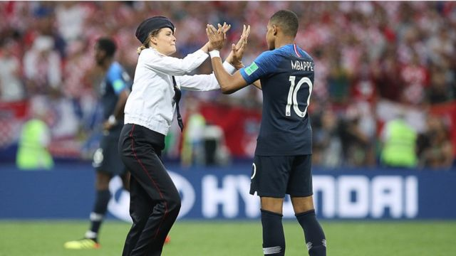 A pitch invader high fives France's Kylian Mbappé during the 2018 FIFA World Cup final football match between France and Croatia, 15 July 2018
