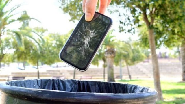 Telefone sendo jogado no lixo