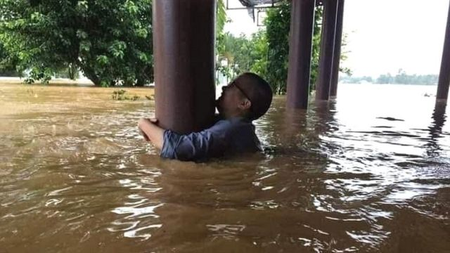 A man grips a post to avoid being swept away in floodwaters in Quang Binh province, Vietnam