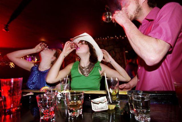 Dos mujeres y un hombre bebiendo en exceso en una barra