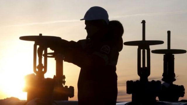 عامل يفحص أنبوبا في حقل نفط في سيبيريا بروسيا