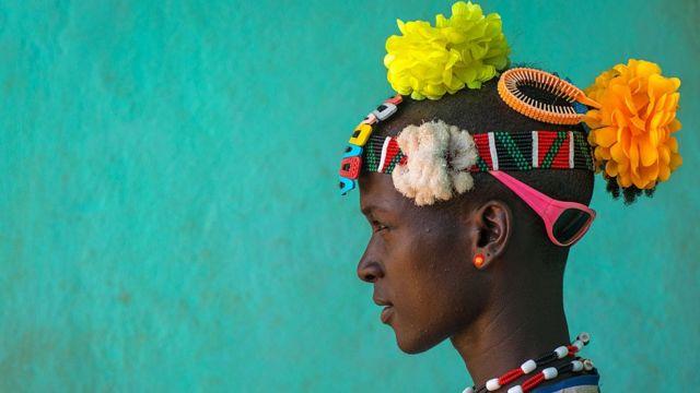 Etiyopyalı Bana kabile üyesinin başında plastik çiçek, güneş gözlüğü ve bantlardan renkli bir kompozisyon.