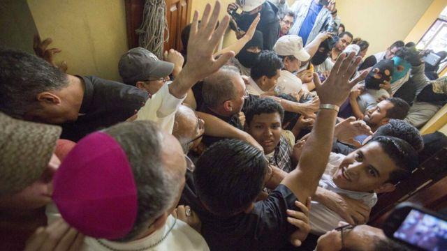 Silvio Báez rodeado de una multitud en la que hay hombres con pasamontañas.