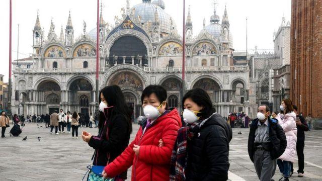 Turistas com máscaras na praça de San Marcos, em Veneza