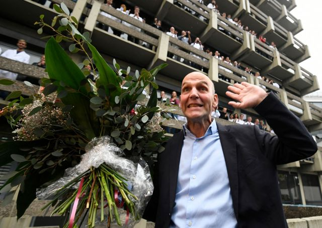 The co-winner of the 2021 Nobel Prize in Chemistry, Germany's Benjamin List, cheers with a bouquet of flowers and is applauded by colleagues at the Max Planck Institute in Muehlheim, Germany, on 6 October 2021