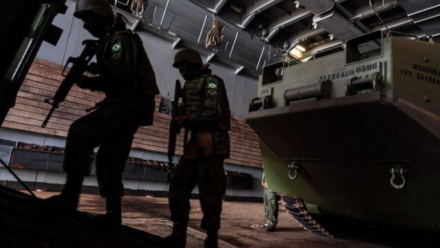 Dois soldados com uniformes do exército brasileiro seguram fuzis em frente a um tanque durante exercício militar