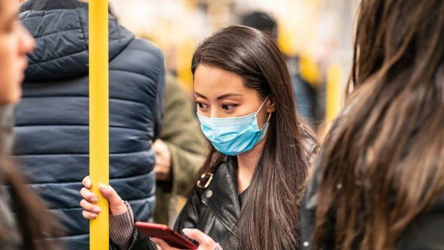 Mulher no metrô com máscara