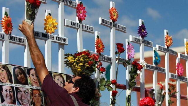 Un pariente de las víctimas del Casino Royale coloca flores en una cruz durante la conmemoración del primer aniversario del crimen en Monterrey, México, el 25 de agosto de 2012. 52 personas murieron el 25 de agosto de 2011, cuando miembros del cartel de drogas Los Zetas roció el Casino Royale con gasolina y lo incendió.