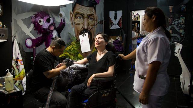 Ana Estrada siendo tatuada en un brazo